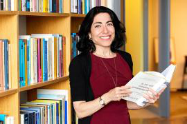 A photo of Jennifer 至ur Chayes holding a book on computer programming in front of a bookshelf